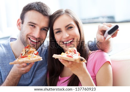 Couple with pizza and TV remote - stock photo