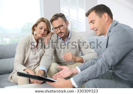 Couple with realtor signing mortgage contract - stock photo