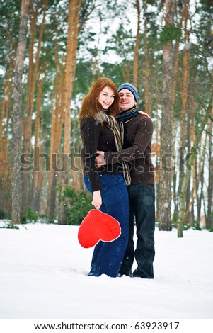 Couple with red heart smiling - stock photo