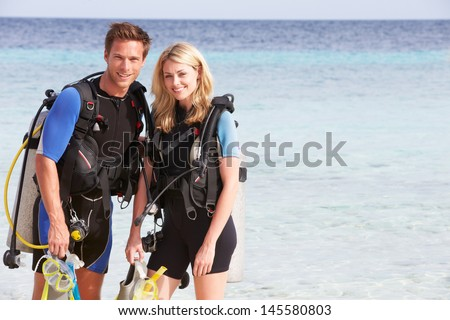 Couple With Scuba Diving Equipment Enjoying Beach Holiday - stock photo