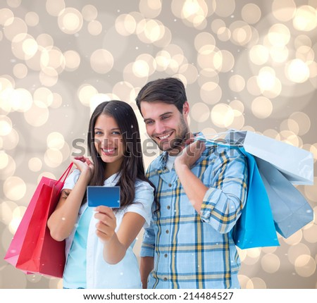 Couple with shopping bags and credit card against light glowing dots design pattern - stock photo