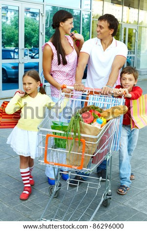 Couple with shopping bags and their two children pushing cart - stock photo