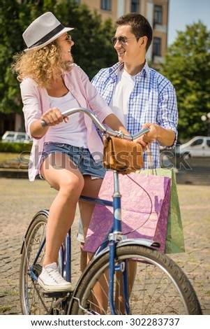 Couple with shopping bags looking to each other while woman riding on bicycle and man standing near her. - stock photo