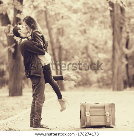 Couple with suitcase kissing at alley in the park. Photo in old color image style. - stock photo
