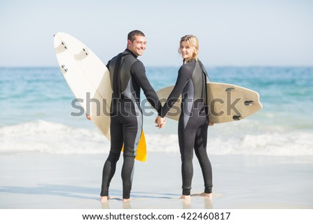 Couple with surfboard holding hand on the beach on a sunny day - stock photo