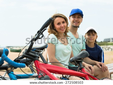 Couple with teenager son sitting at seashore in summer day with cycles - stock photo