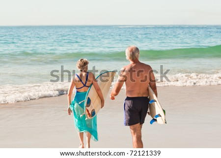 Couple with their surfboard on the beach - stock photo