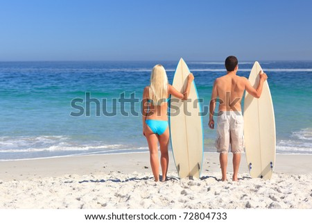 Couple with their surfboards - stock photo