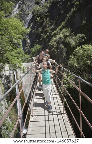 Couple with three children crossing bridge in mountains - stock photo