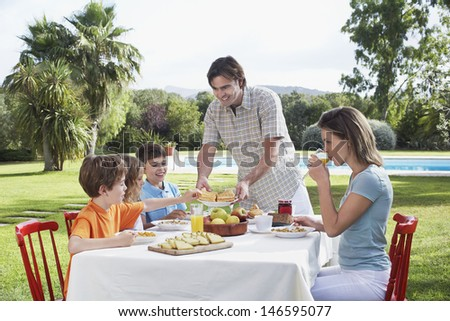 Couple with three children sitting at breakfast table outdoors - stock photo