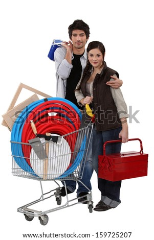 Couple with trolley full of DIY equipment - stock photo