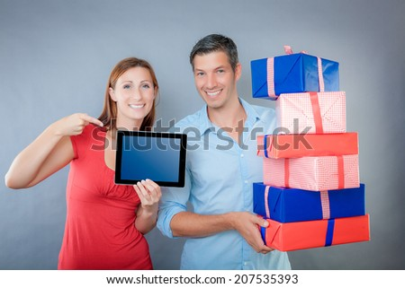 couple with woman advertising with finger on tablet - stock photo