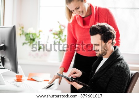 Couple working in home office with phone and computer - stock photo