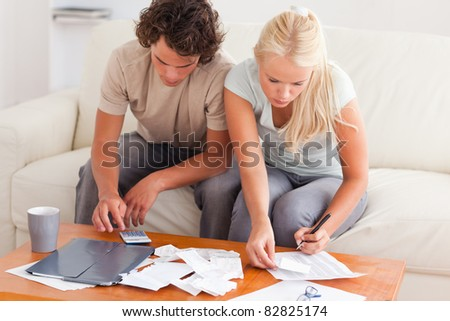 Couple working together in the living room - stock photo