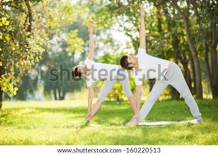 Couple Yoga, man and woman doing yoga exercises in the park - stock photo