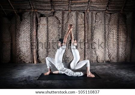 Couple yoga of woman and man doing ashwa sanchalanasana lunge pose in white cloth in yoga hall, Varkala, Kerala, India - stock photo