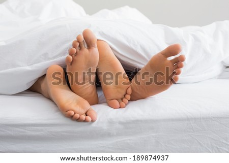 Couples feet sticking out from under duvet at home in bedroom - stock photo