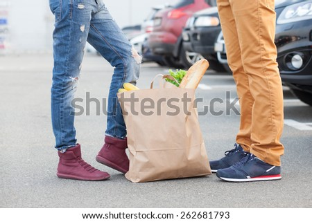 Couples foot and shopping bag with food - stock photo