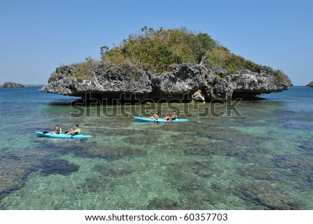 Couples kayaking by a beautiful island beach with pristine waters in the Hundred Islands, Philippines. - stock photo
