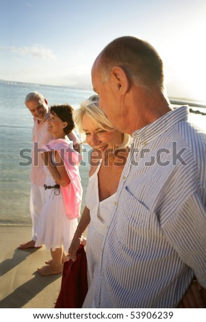 Couples of smiling seniors having a walk at the water's edge - stock photo