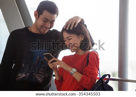couples of younger asian man and woman relaxing with happy face reading text on smart phone use for people and modern lifestyle  - stock photo