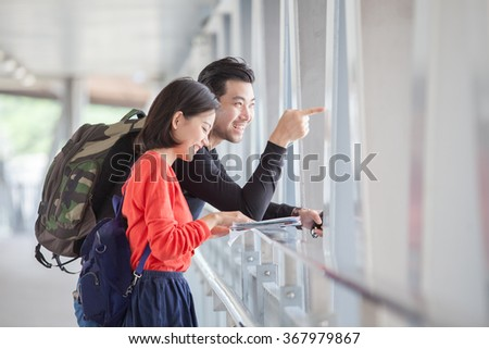 couples of younger traveling man and woman looking to traveler guide book on location - stock photo