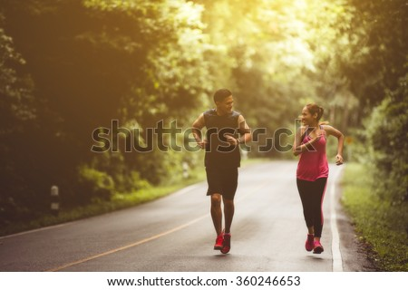 Couples take vacations jogging in the forest. The integrity and refreshing - stock photo