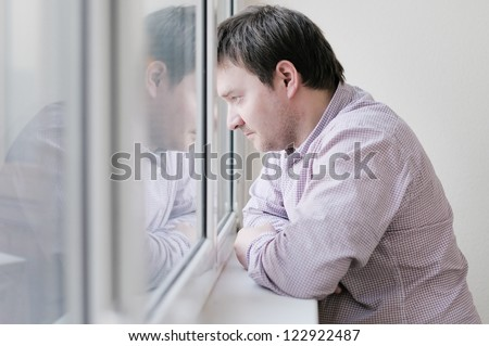 Courageous middle age man looking at the window - stock photo