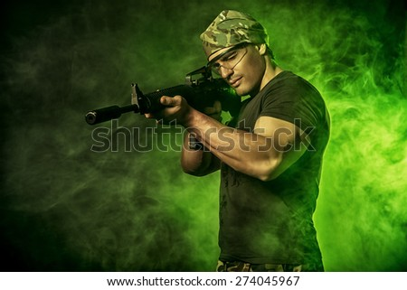 Courageous soldier in camouflage holding automatic rifle. Military. - stock photo