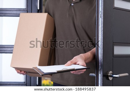Courier asking customer for a sign on documents - stock photo