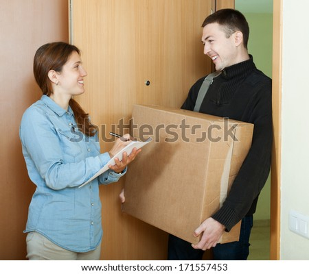 Courier delivered  a parcel to woman - stock photo