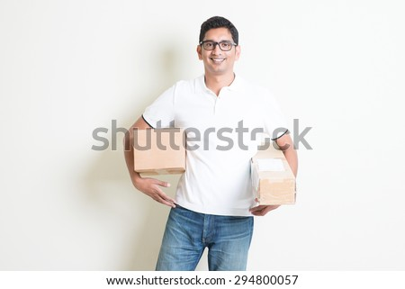 Courier delivery service concept. Happy Indian man received brown boxes, standing on plain background with shadow. Asian handsome guy model.  - stock photo