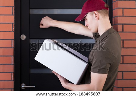 Courier knocking on a customer's door, horizontal - stock photo