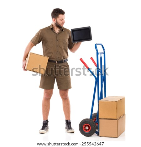 Courier showing schedule. Cheerful delivery man standing with package under his arm and holding digital tablet. Full length studio shot isolated on white. - stock photo
