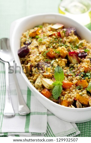 Couscous and roasted vegetables salad in a white dish - stock photo