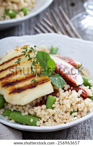 Couscous salad with green beans, figs and cheese - stock photo