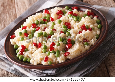 Couscous salad with green peas and pomegranate close-up on the table. horizontal - stock photo
