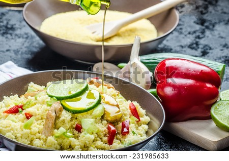 Couscous with grilled chicken meat and vegetables, fresh lime on top - stock photo