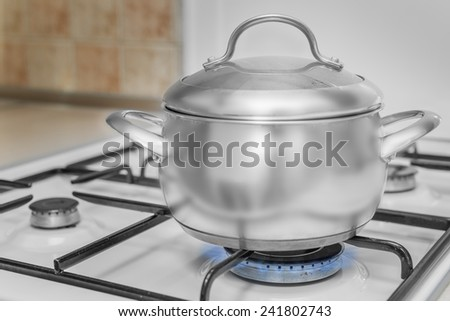 Cover pan on the stove burning flame - stock photo
