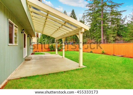 Covered backyard patio with concrete floor. Fenced brown backyard and well kept green lawn around - stock photo