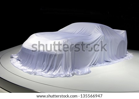 Covered car. Sport car covered with a white cloth in a exhibition on black background - stock photo