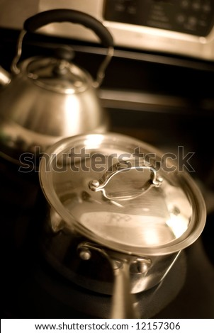 Covered cooking pot and tea kettle on a stovetop in warm sepia tones with selective focus. Focus on lid handle. - stock photo