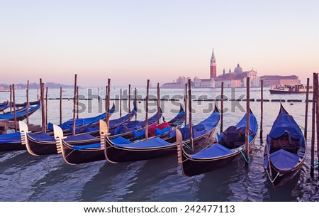 covered gondolas in Venice lagoon at sunset - stock photo