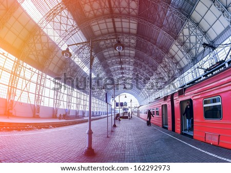 Covered railway station with train and silhouettes of hurrying people. Young man in the tambour train - stock photo
