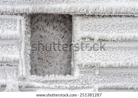 Covered with hoarfrost wall of the wooden house  - stock photo