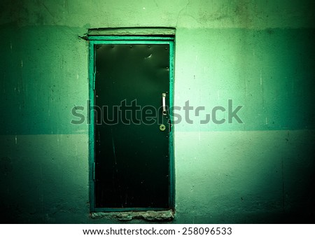 Covered with leather door with white metal handle and plastered wall around. Toned green. - stock photo