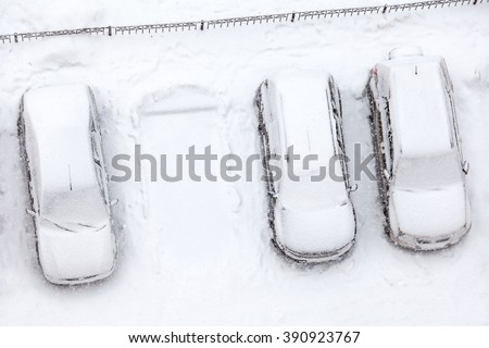 Covering with snow line of standing car with free parking place, winter and snowfall - stock photo