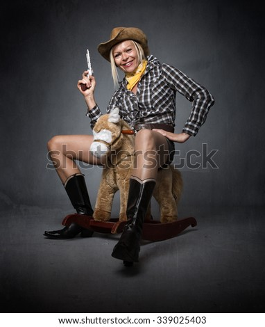 cow boy funny portrait, with gun and fake horse - stock photo