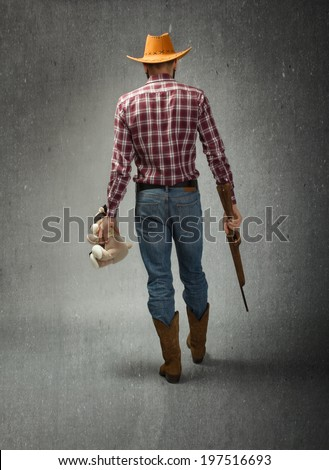 cow boy wins a teddy bear on aiming game - stock photo
