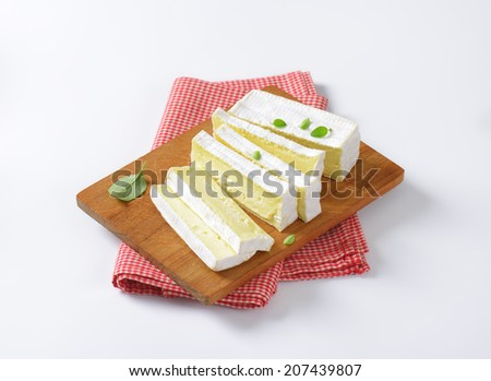 cow's milk cheese with white mold, served on the wooden cutting board with fabric linen - stock photo